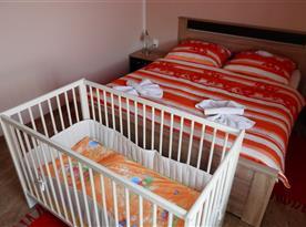 ložnice s manželským lůžkem a dětskou postýlkou