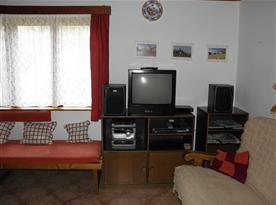 Společenská místnost s pohovkou, stolem, lavicí a televizí