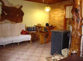 Společenská místnost s pohovkou, stolem, lavicí a krbem