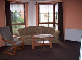 Obývací pokoj s pohovkou, křeslem a stolkem