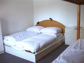Ložnice s manželskou postelí a prádelníkem