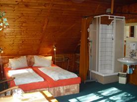 Podkrovní pokoj s manželskou postelí, sprchovým koutem a umyvadlem