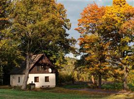 Celkový pohled na chatu umístěnou na polosamotě za krásného podzimního dne