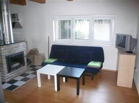 Společenská místnost s krbem, posezením a televizí