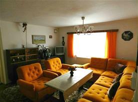 Obývací pokoj se sedací soupravou a televizí se satelitem