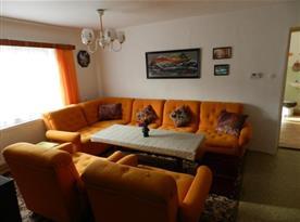 Obývací pokoj s rohovou sedačkou, křesly, televizí a satelitem