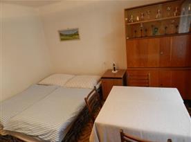 Ložnice s manželskou postelí, stolem a židlemi