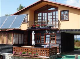 Pohled na chatu s terasou a balkónem