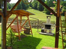 Udržovaná zahrada s dřevěnou houpačkou