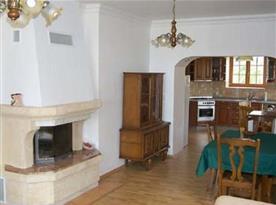 Obývací pokoj s krbem, stolem, židlemi a pohledem do kuchyně