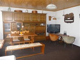 Obývací pokoj s televizí, satelitem, stolem, židlemi a sedací soupravou