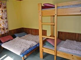 Chatka s patrovou postelí, lůžky, stolem, židlemi a skříní