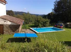 Pohled z terasy přes dvůr s bazénem do údolí
