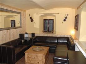 Obývací pokoj v přízemí s krbem, rozkládací sedačka