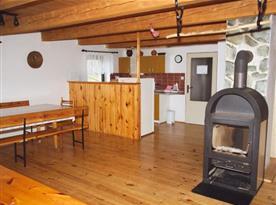 Obývací pokoj se stoly, lavicemi, kamny a propojen s kuchyní