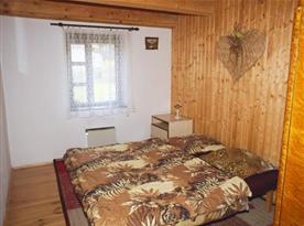 Ložnice v přízemí s lůžky, nočním stolkem, skříní a lampičkou