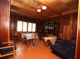 Obývací pokoj s rozkládacím gaučem, stolem, židlemi a televizí