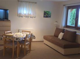 Pokoj (obývací a jídelní část) - pohled z ložnice; rozkládací gauč - slouží jako 3.+4. přístýlka