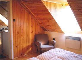 Podkrovní ložnice s lůžky, skříní a křeslem