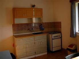 Kuchyňka se sporákem, lednicí, varnou konvicí a mikrovlnou troubou