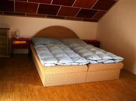 Podkrovní ložnice s lůžky a skříní