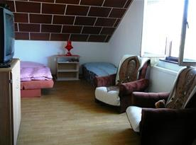 Podkrovní ložnice s lůžky, křesly a televizí
