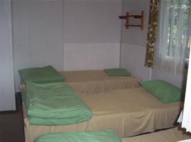 Chata s lůžky, skříní, židlemi, stolkem a lampičkou