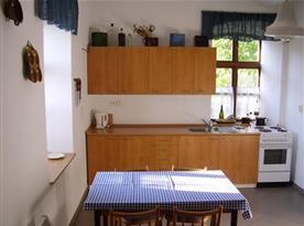 Kuchyně se sporákem, lednicí, varnou konvicí a stolem