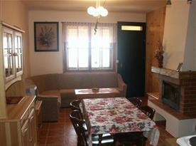Obývací pokoj s krbem, pohovkou, stolkem, kredencem a televizí