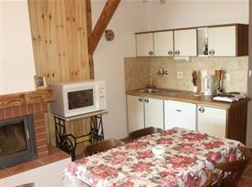 Kuchyňský kout s vařičem, ledničkou, varnou konvicí, stolem a židlemi