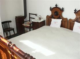Ložnice s lůžky, nočním stolkem, židlí a kamny