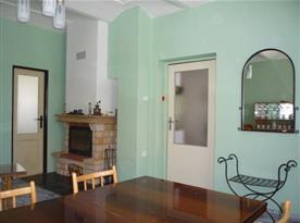 Obývací pokoj se sedací soupravou, stolem, židlemi, televizí a krbem