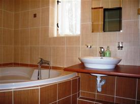 Koupelna s rohovou vanou a umývadlem