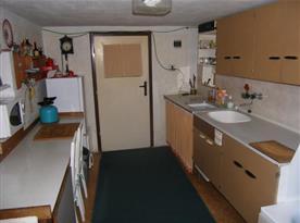 Kuchyně s vařičem, varnou konvicí a vanou oddělenou závěsem
