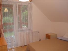 Pohled na pokoj D s manželským lůžkem, nočním stolkem a komodou