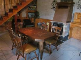 Společenská místnost se stolem, židlemi, krbem a schody do podkroví