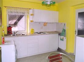 Kuchyně s varným panelem, ledničkou, varnou konvicí a pračkou