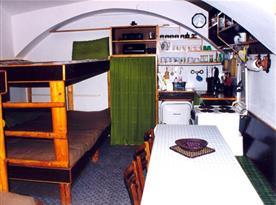 Obytná místnost s patrovou postelí, kuchyňským koutem a jídelním koutem