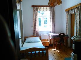 Pokojík B s lůžkem, stolem, židlemi a kamny