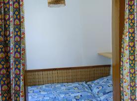 Dvojlůžko vedle pokojíku B s lůžkem, stolem, židlemi a kamny