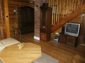 Obývací pokoj s televizí a schody do podkroví