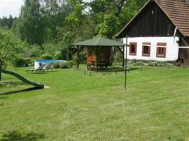 Zahrada s hřištěm, skluzavkou a posezením