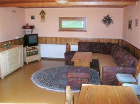 Společenská místnost s rohovou sedačkou, stolkem, taburety a televizí