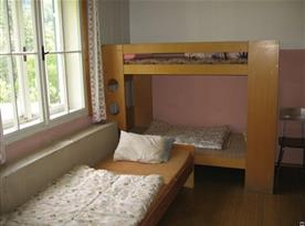 Pokoj s lůžky, patrovou postelí, skříní, stolem a židlemi