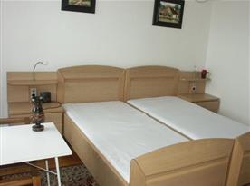 pokoj s lůžky, skříní, nočním stolkem a lampičkou