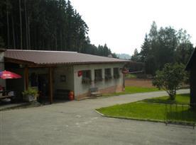 Pohled na budovu s restaurací v pozadí s volejbalovým hřištěm