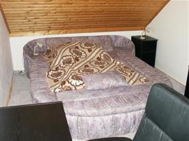Pokoj s lůžky, stolem, nočním stolkem, lampičkou, židlí a skříňkou