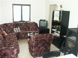 Obývací pokoj s rohovou sedací soupravou, stolkem, skříňkou a televizí