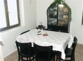 Obývací pokoj se stolem, židlemi a sekretářem