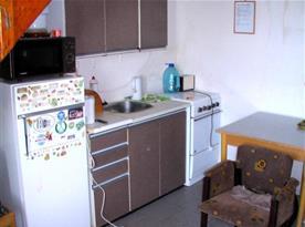 Menší kuchyně se sporákem, ledničkou, varnou konvicí, stolem a židlemi